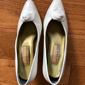 Used white pump with rose embellishment near toe